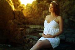 Härlig gravid kvinna som trycker på hennes buk Royaltyfri Fotografi