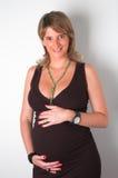 Härlig gravid kvinnaholding henne buk Arkivbild