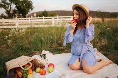 Härlig gravid kvinnashow och att äta det röda äpplet sund mat nya frukter Lyckligt kvinnaleende arkivfoton
