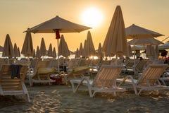 Härlig gul himmel och många sunchairs, solparaplyer och slags solskydd på en strand i Albanien den sena eftermiddagen arkivfoto