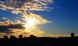 Härlig gul solnedgång med konturbyggnader, grå färgmoln och blå himmel royaltyfri bild