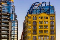Härlig gul tappningbyggnad med en annan byggnad, som har mycket exponeringsglasfönster, stadsarkitektur av Blankenberge, arkivbilder