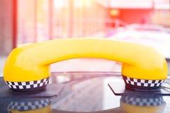 Härlig gul telefonlur med taxisymboler på taket av bilen royaltyfri fotografi