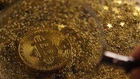 Härlig guld- Bitcoin för förstoringsapparatshower modell Macro arkivfilmer