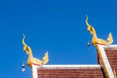 Härlig guld- naga skulpterar på det kyrkliga taket under bakgrunden för blå himmel på Wat Phra That Doi Tung, en av som är motsäg Arkivfoto