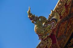 Härlig guld- naga skulpterar på det kyrkliga taket under bakgrunden för blå himmel på Wat Phra That Doi Tung, en av som är motsäg Arkivbild
