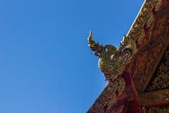 Härlig guld- naga skulpterar på det kyrkliga taket under bakgrunden för blå himmel på Wat Phra That Doi Tung, en av som är motsäg Royaltyfri Foto
