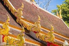 Härlig guld- naga skulpterar på det kyrkliga taket under bakgrunden för blå himmel på Wat Phra That Doi Tung, en av som är motsäg Arkivfoton