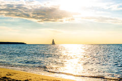 Härlig guld- solnedgång över havet med skeppet på horisont Arkivfoton
