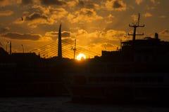 Härlig guld- solnedgång bak en svart kontur av en bro och byggnader i Istanbul arkivbilder