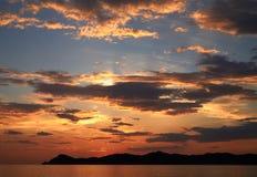 Härlig guld- solnedgång med clousy himmel royaltyfri foto