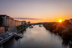 Härlig guld- sommarsolnedgång i Stockholm Sverige Perspektiv av vattenkanalen med fartyg och byggnader arkivbilder