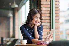 Härlig gullig asiatisk ung affärskvinna i kafét som tar sel royaltyfria bilder