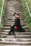 Härlig gullig flicka i röd hatt och svart lag som går i staden Royaltyfri Bild