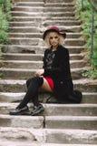 Härlig gullig flicka i röd hatt och svart lag som går i staden Arkivbilder