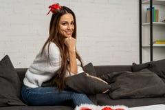 Härlig gullig kvinna i den santa hatten som sitter på soffan och poserar med att le framsidan royaltyfria foton