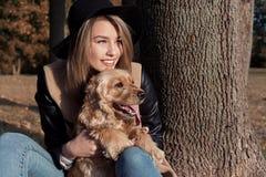Härlig gullig lycklig flicka i en svart hatt som spelar med hennes hund i en parkera Royaltyfria Bilder