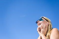 Härlig hållande ögonen på film för ung dam med exponeringsglas 3D, blå ljus bakgrund Royaltyfri Foto