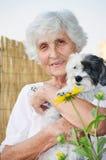 Härlig hög kvinna som kramar hennes hund Arkivfoto