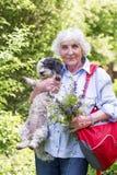 Härlig hög kvinna som kramar hennes hund Arkivbild