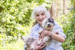 Härlig hög kvinna som kramar hennes hund Royaltyfri Bild