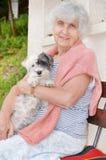 Härlig hög kvinna som kramar hennes vita hund i berget Arkivbilder