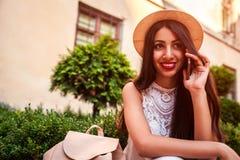 Härlig högskolaflicka som utomhus talar på telefonen Mitt - östlig kvinna som kallar vänner Royaltyfri Foto