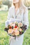 Härlig höstbukett för närbild i händer blommaordning med olika blommor grön gräsmatta på bakgrund brigham arkivbild
