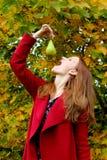 Härlig höstlövverk på en naturkvinna avgjorde att äta det gröna päronet royaltyfria bilder