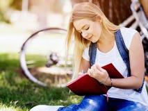 Härlig handstil för ung kvinna i hennes dagbok utomhus Fotografering för Bildbyråer