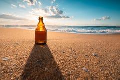 Härlig havssoluppgång och ölflaska på strandsanden arkivbild