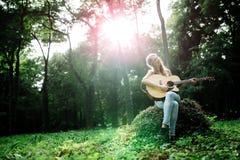 Härlig hippie som spelar gitarren Arkivbilder