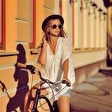 Härlig hipsterflicka på en cykel fotografering för bildbyråer