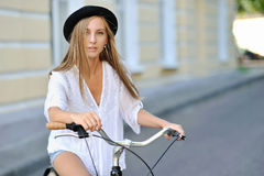 Härlig hipsterflicka på en cykel royaltyfria foton