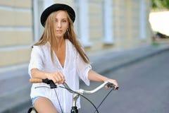 Härlig hipsterflicka på en cykel royaltyfri bild