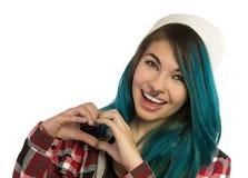 Härlig hipsterflicka som ler, medan göra en gest hjärtatecknet royaltyfria foton