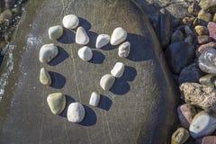 Härlig hjärta som göras av stenar över vagga Arkivbilder