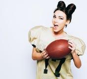 Härlig idrotts- brunettflicka i likformign för amerikansk fotboll som visar bollen som har gyckel Super Bowl footy royaltyfri fotografi