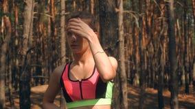 Härlig idrotts- flicka som vilar i skogen arkivfilmer