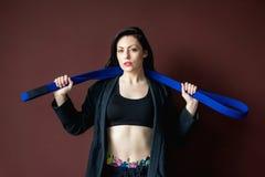 H?rlig idrotts- kvinna f?r st?ende i svart kimono med det bl?a b?ltet Kampsportbegrepp Inomhus studioskott, bakgrund arkivbild