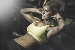 Härlig idrotts- kvinna som arbetar ab-mellanrum i kondition Arkivfoton