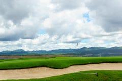 härlig idyllisk siktsgräsplan med sandfälla och den vita flaggan och sikt av berget, blå himmel med moln Royaltyfri Bild