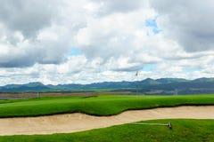 härlig idyllisk siktsgräsplan med sandfälla och den vita flaggan och sikt av berget, blå himmel med moln Fotografering för Bildbyråer