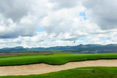 härlig idyllisk siktsgräsplan med sandfälla och den vita flaggan och sikt av berget, blå himmel med moln Royaltyfria Bilder