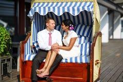 Härlig indisk brud och caucasian brudgum, i strandstol. Royaltyfri Fotografi