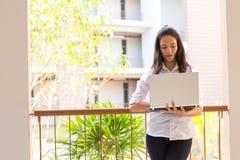Härlig indisk högskolaflicka som använder bärbara datorn med den selektiva fokusen Arkivfoton
