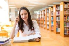 Härlig indisk högskolaflicka som läser en bok i arkiv med se Royaltyfri Fotografi