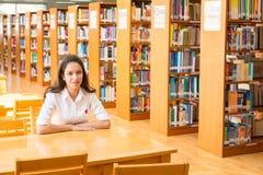 Härlig indisk högskolaflicka som läser en bok i arkiv med se Royaltyfria Foton