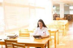 Härlig indisk högskolaflicka som läser en bok i arkiv med se Arkivbilder