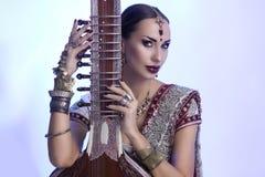 Härlig indisk kvinna i sari med orientaliska smycken som poserar med Fotografering för Bildbyråer